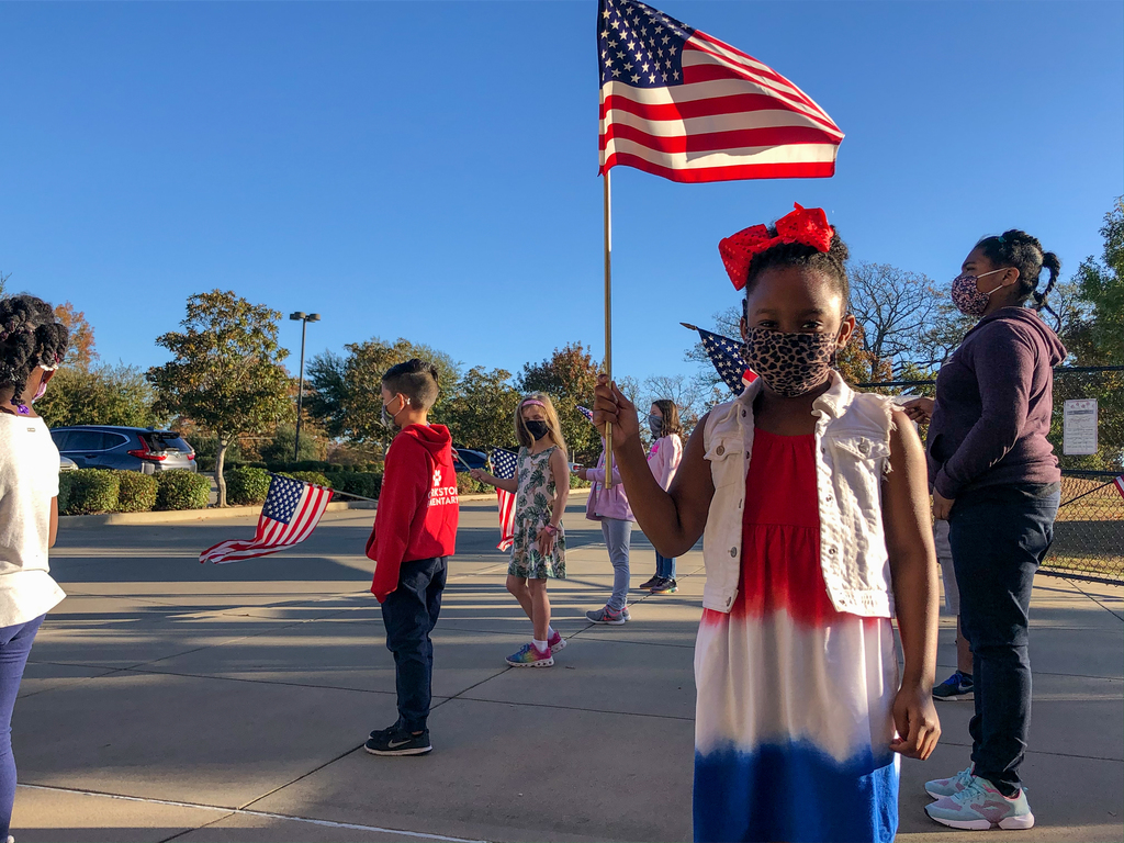 A Clarkston Elementary student holding a flag during a veterans day event.