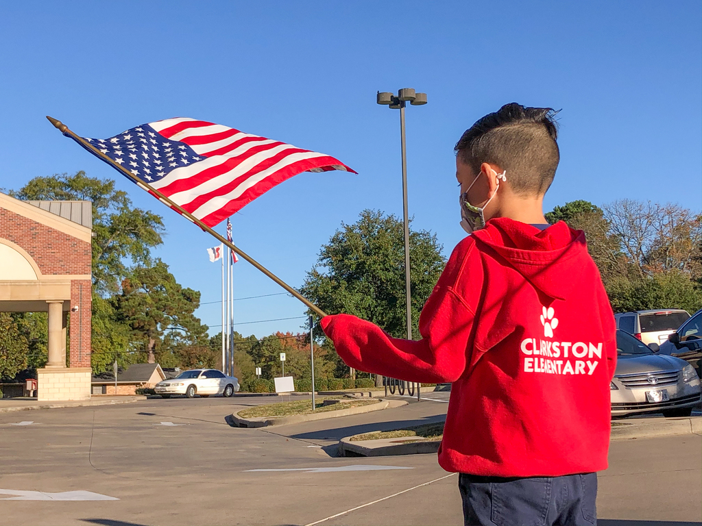 Clarkston Elementary student waving a US flag.