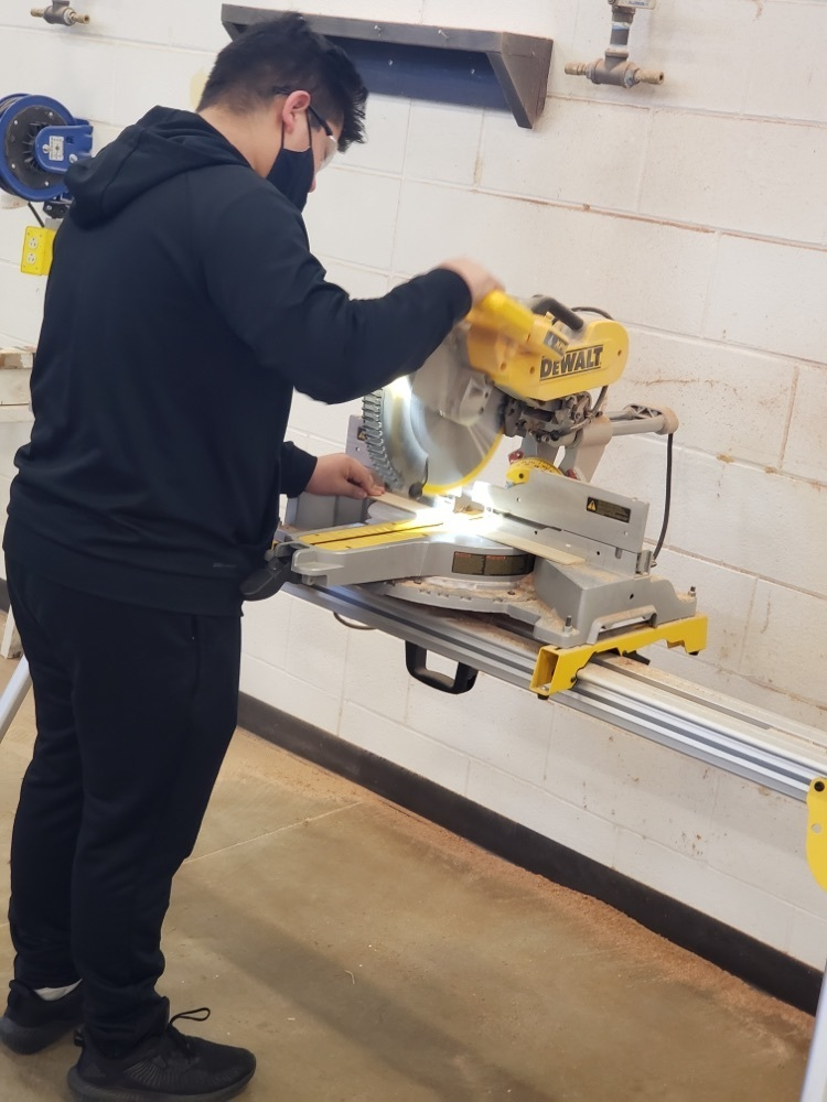Student using a cutting machine to cut wood.