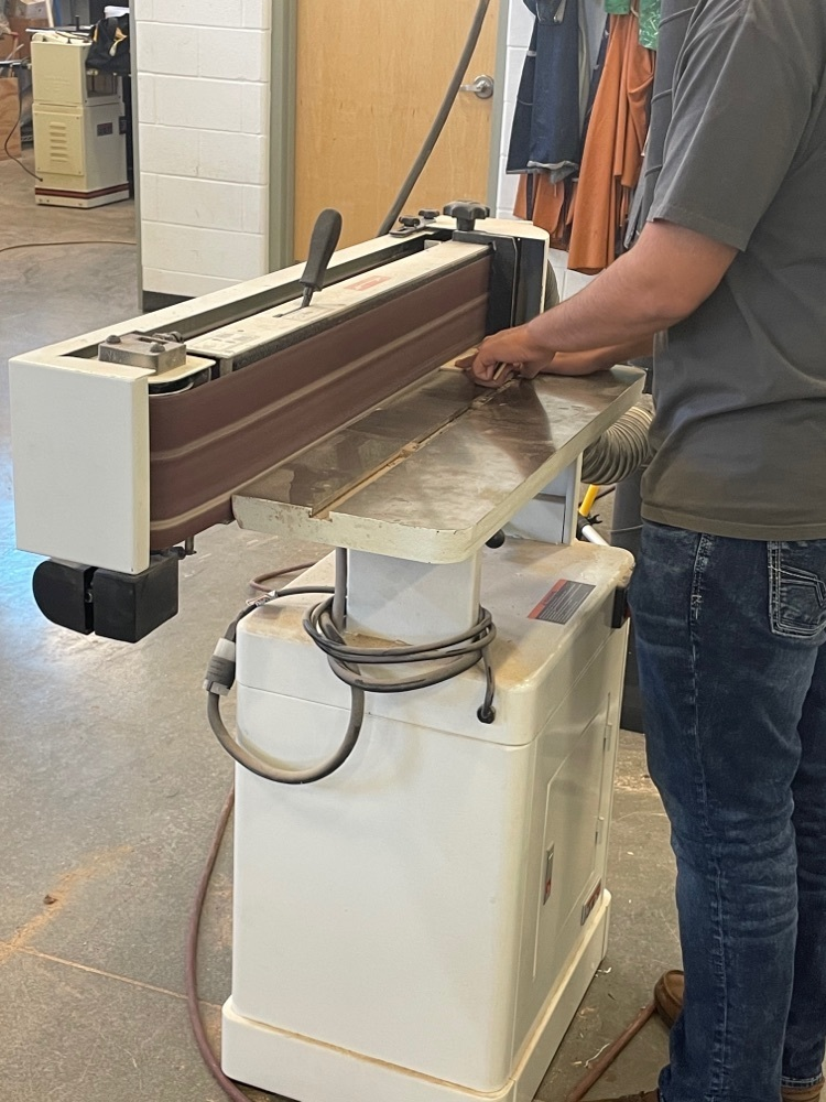 Student using a sanding machine.