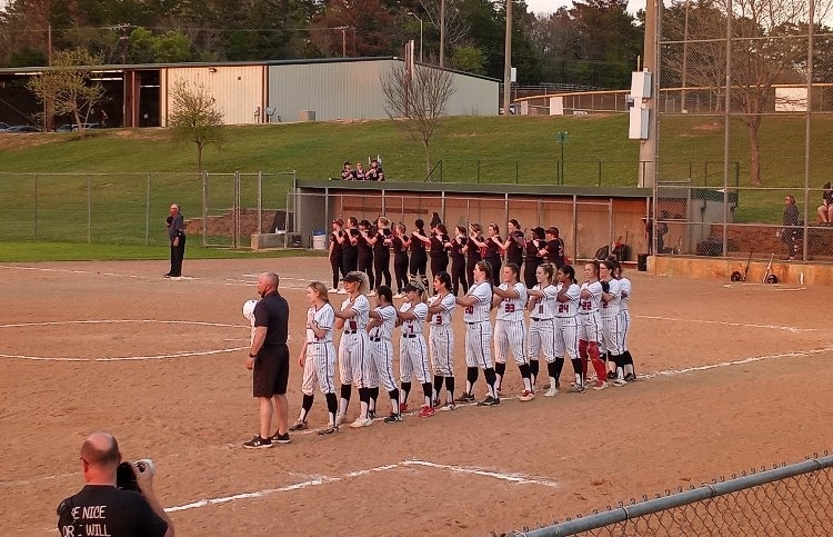varsity lady raiders standing for the singing of the national anthem